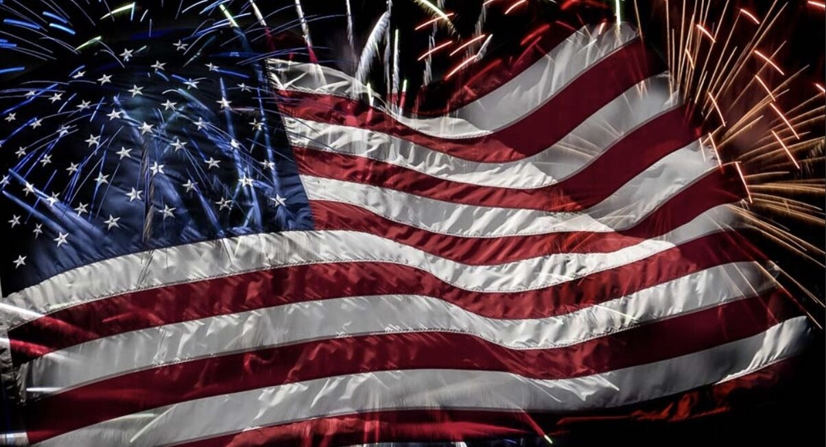 American flag with fireworks behind it