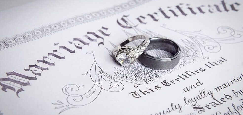 two wedding rings sitting on a marriage license